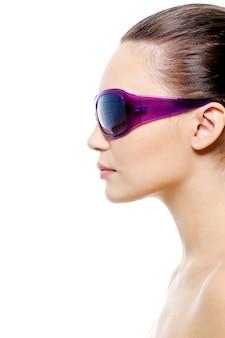 Profiel portret van een jong vrouwelijk gezicht in violet zonnebril