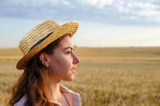 Profiel portret van een jonge vrouw in strooien hoed in een tarweveld bij dageraad, kopieer ruimte