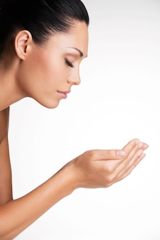 Profiel portret van een mooie jonge vrouw met handen op het gezicht. schoonheidsbehandeling concept