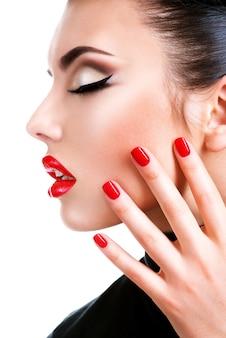 Profiel portret van een mooie jonge vrouw met rode lippenstift. mannequin met heldere glamourmanicure.