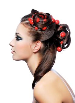 Profiel portret van een schattige jonge vrouw met creativiteit kapsel en fashion make-up
