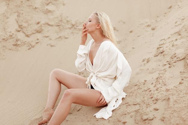 Profiel portret van een sexy jonge blonde vrouw in wit groot overhemd, rokende zittend op de zandgrond. buiten portret.