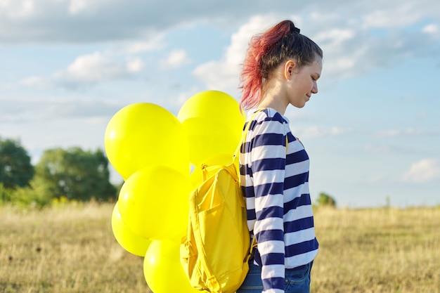 Profiel portret van gelukkig tienermeisje 15 jaar oud met gele ballonnen. hemel in wolken, aardachtergrond. vakantie, natuur, tieners, vreugdeconcept