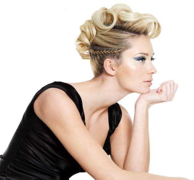 Profiel portret van glamour jonge vrouw met krullend, vlecht kapsel geïsoleerd op een witte muur