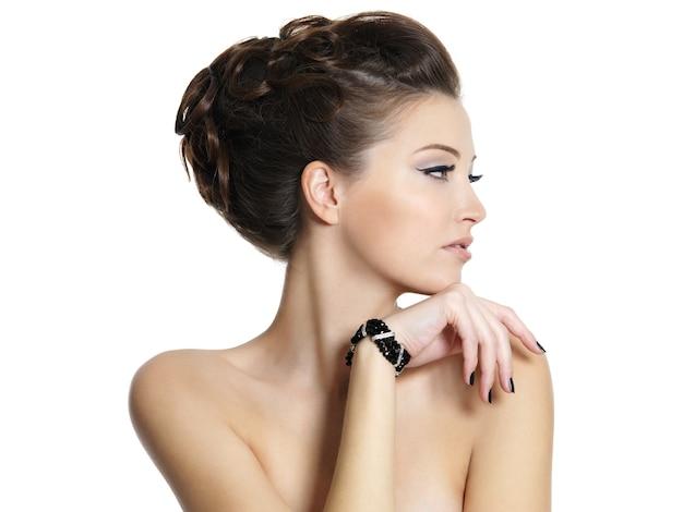 Profiel portret van het mooie jonge meisje met krullend kapsel -