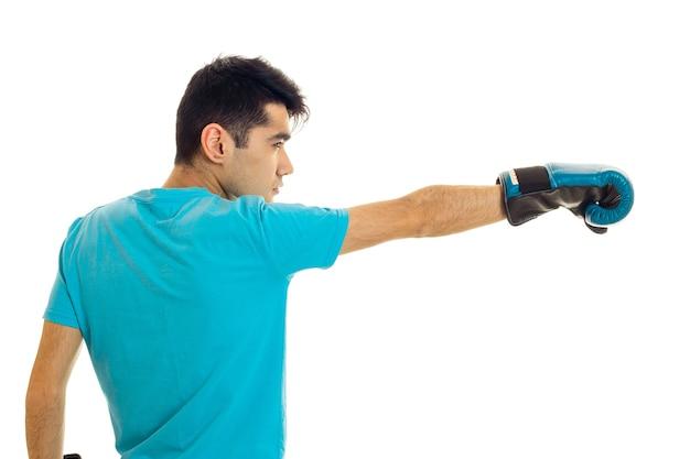 Profiel portret van jonge brunette man in blauwe bokshandschoenen oefenen geïsoleerd op een witte muur