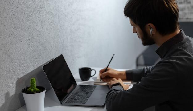 Profiel portret van jonge zakenman maken van aantekeningen in notitieblok