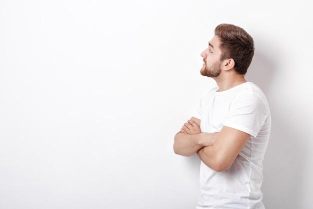 Profiel portret van knappe jonge man met baard op zoek naar de kant voor de witte muur. kopieerruimte