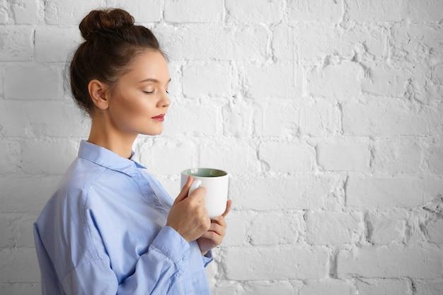 Profiel portret van stijlvolle vermoeide jonge zakenvrouw met make-up en haar broodje ontspannen in kantoor met kopje verse sterke drank tijdens koffiepauze, ogen sluiten, poseren op bakstenen muur, mok bedrijf