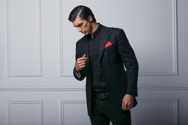 Profiel portret van zelfverzekerde jonge man in zwart pak met rode zijden sjaal in zak, naar beneden te kijken, over grijze achtergrond.