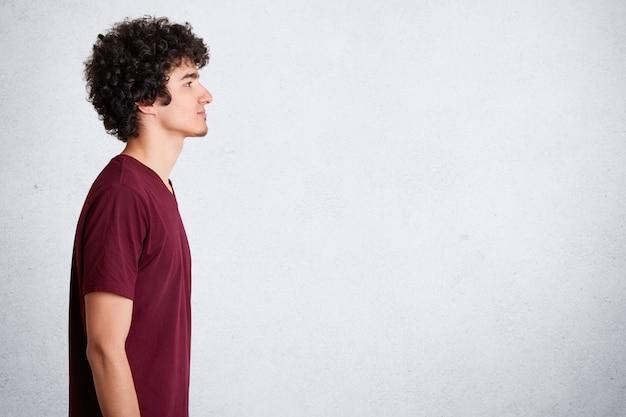 Profiel schot van knappe jonge man met donker krullend haar, gekleed casual kastanjebruine t-shirt, kijkt naar kopie ruimte, staat tegen witte muur met vrije ruimte voor uw advertentie of promotionele tekst.