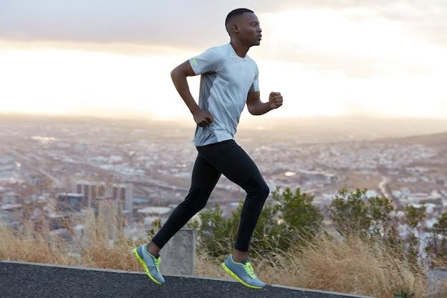 Profiel shot van energieke donkere man loopt op snelweg tegen heldere hemel met ochtendlicht, draagt casual comfortabele t-shirt, legging en trainers, geniet van vrije tijd in de zomer