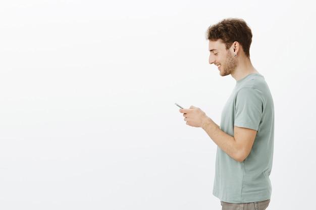 Profiel shot van vriendelijke knappe jonge mannelijke model in oorbellen, smartphone in handen houden, breed glimlachend op scherm, tevreden met leuk bericht van vriend