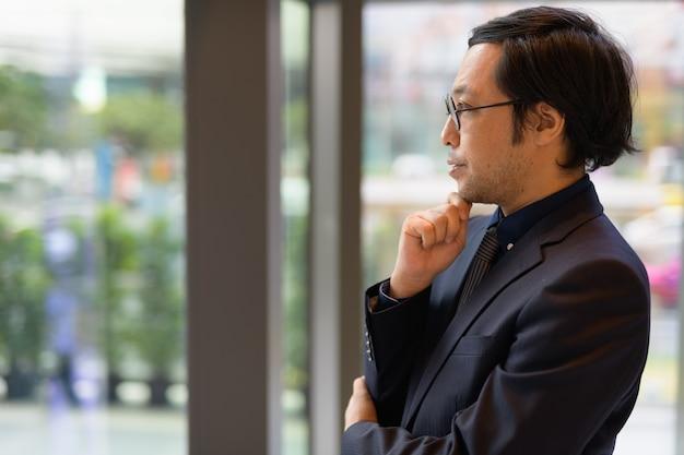 Profiel te bekijken van aziatische zakenman denken en kijken door t