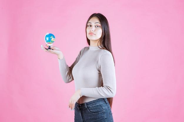 Profiel te bekijken van een meisje met een mini-wereldbol met vertrouwen