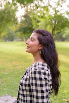 Profiel te bekijken van gelukkige jonge mooie indiase vrouw die lacht met gesloten ogen in het park buiten