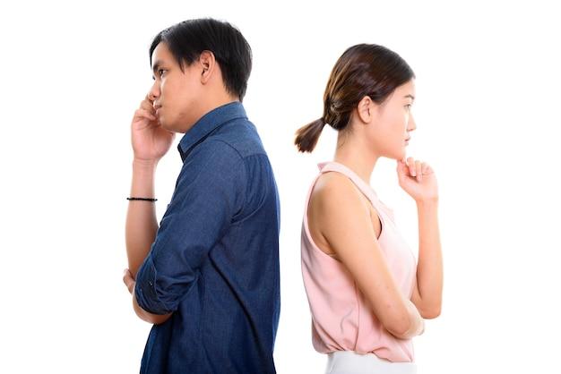 Profiel te bekijken van jonge aziatische paar denken samen met rug tegen elkaar
