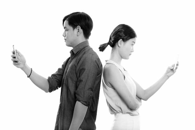Profiel te bekijken van jonge aziatische paar met behulp van mobiele telefoon samen met rug tegen elkaar