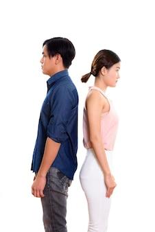 Profiel te bekijken van jonge aziatische paar met rug tegen elkaar geïsoleerd