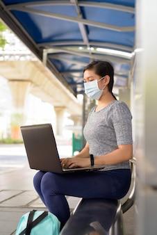 Profiel te bekijken van jonge aziatische vrouw met masker met laptop zittend bij de bushalte