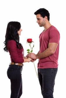 Profiel te bekijken van jonge gelukkige paar glimlachen en staan terwijl het houden van roos