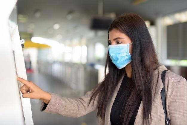 Profiel te bekijken van jonge indiase zakenvrouw met masker kaartje kopen bij skytrain station