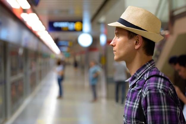 Profiel te bekijken van jonge knappe toeristische man trein te wachten