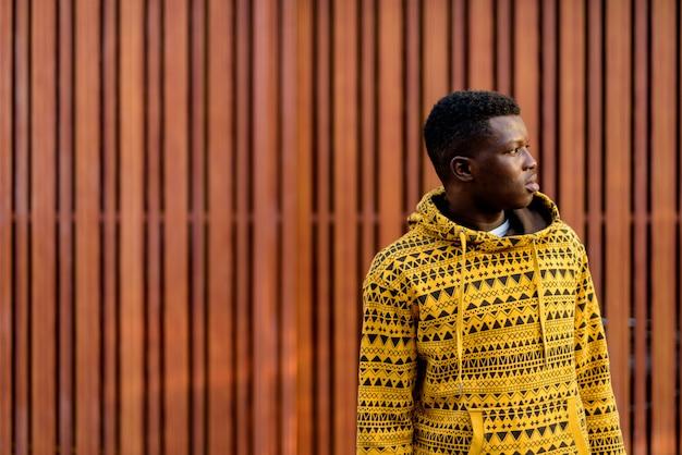 Profiel te bekijken van jonge man denken tegen houten muur