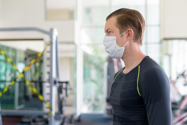 Profiel te bekijken van jonge man met masker voor bescherming tegen uitbraak van het coronavirus in de sportschool tijdens coronavirus covid-19