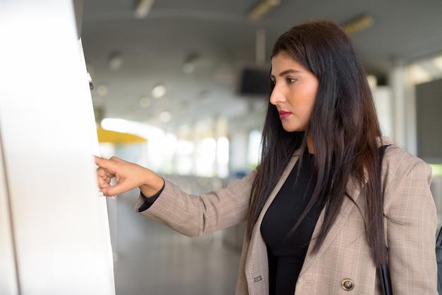 Profiel te bekijken van jonge mooie indiase zakenvrouw kaartje kopen bij skytrain station