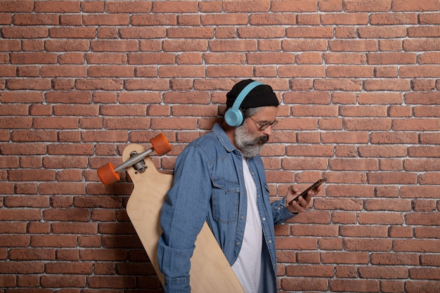 Profiel te bekijken van moderne man met baard, hoed, koptelefoon en longboard telefoon kijken op bakstenen muur