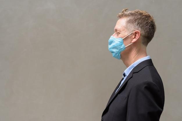 Profiel te bekijken van volwassen zakenman met masker voor bescherming tegen uitbraak van het coronavirus buitenshuis