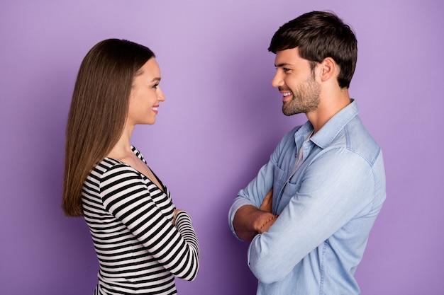 Profiel twee mensen koppel kerel dame staande tegenover kijkende ogen armen gekruist vriendelijk glimlachen draag stijlvolle casual outfit geïsoleerde pastel paarse kleur muur