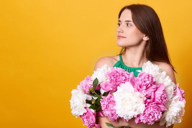 Profiel van brunette jonge dame draagt groene kleding, omhelst enorme boeket pioenrozen