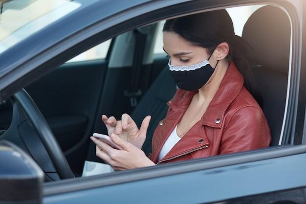 Profiel van drukke ernstige jonge vrouwelijke rijdende auto, het dragen van medische masker voor bescherming, het vasthouden van mobiele telefoon, het gebruik van apparaat, het lezen van nieuws, aandachtig kijken naar het scherm.