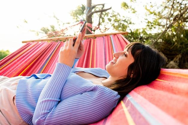Profiel van een blanke vrouw die een telefoon gebruikt die in een hangmat ligt te glimlachen