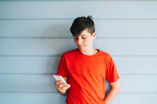 Profiel van een gelukkige mannelijke tiener die op een slimme telefoon texting