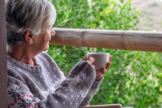 Profiel van een grijsharige oudere vrouw in een wintertrui zittend op het houten balkon kijkend naar het bos met een kopje koffie.