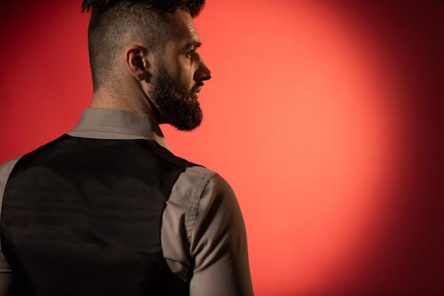 Profiel van een jonge ernstige bebaarde man in een zwart vest op rode achtergrond. achteraanzicht ruimte voor tekst
