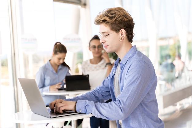 Profiel van een jonge man met piercings die op laptop werkt