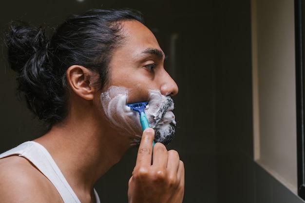 Profiel van een latino man die een scheermesje gebruikt in de badkamer van zijn huis