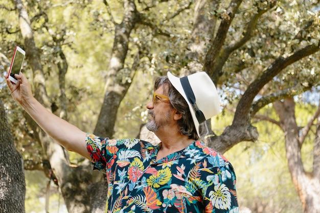 Profiel van een man hoed met een bloemenprint shirt maken een selfie in een tuin