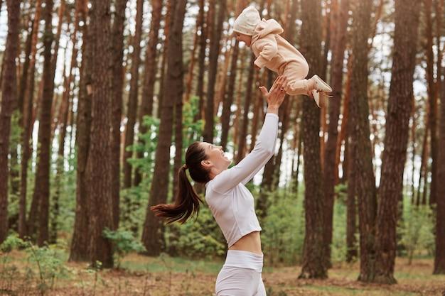 Profiel van een moeder die speelt met een babymeisje, een vrouw die een kleine dochter in de lucht overgeeft, een gelukkige familie die buiten plezier heeft