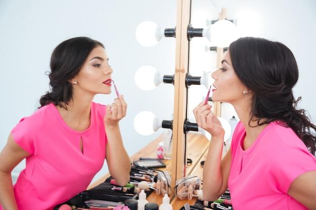 Profiel van een mooie jonge vrouw die in de buurt van de spiegel staat en lippenborstel gebruikt voor het aanbrengen van rode lippenstift