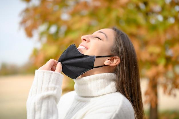 Profiel van een ontspannen vrouw die masker opstijgt en frisse lucht inademt in een park in tijden van coronavirus