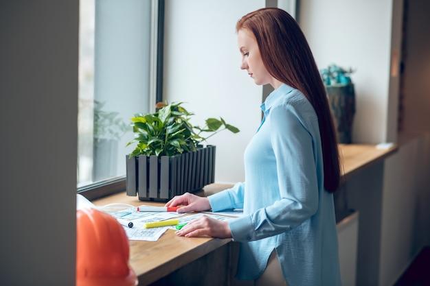 Profiel van een vrouw die werkt met blauwdrukken bij het raam