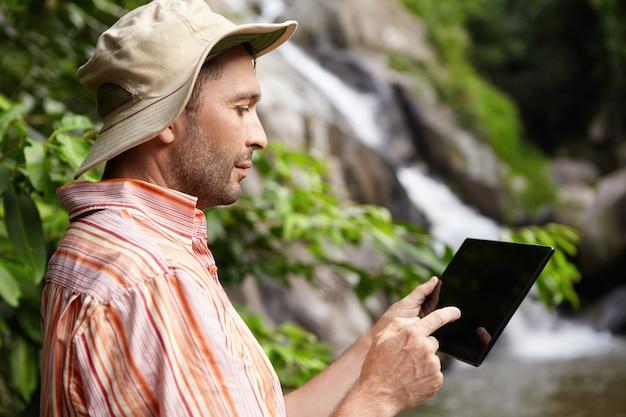 Profiel van :: ernstige mannelijke wetenschapper met stoppels nemen foto van de natuur op zijn zwarte generieke digitale tablet tijdens het werken aan wetenschappelijk onderzoek in de jungle.