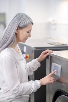 Profiel van :: ernstige volwassen vrouw met lang grijs haar vinger aan het bedieningspaneel van de wasmachine aan te raken