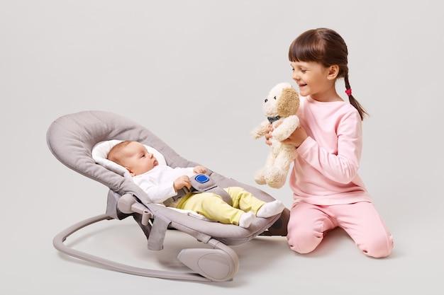 Profiel van :: glimlachend kleuter meisje met pigtails zacht hondenstuk speelgoed tonen aan haar pasgeboren zus liggend in uitsmijter schommelstoel