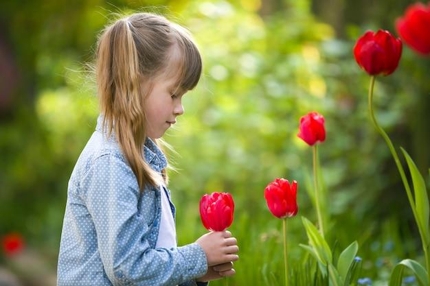 Profiel van kindmeisje die rode tulpenbloem ruiken